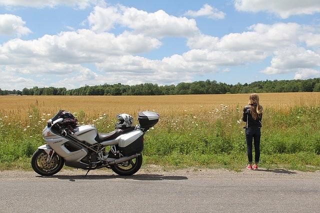 Tjej som är ute på roadtrip med sin motorcykel.